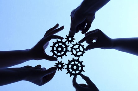 Picture of 5 hands piecing gears together